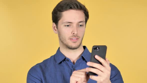 Thumbnail for Man Using Smartphone on Yellow Background