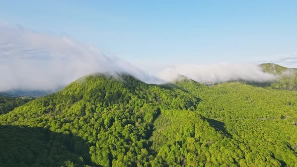 Aerial View Hyperlapse of Green Mountains Covered with Morning Clouds