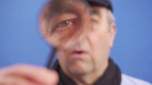 A Funny Mature Man Looks at the Camera with a Magnifying Glass Looking for Valuable Information
