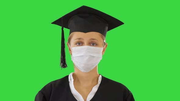 Graduate Student Lady in a Medical Mask Looking To Camera on a Green Screen, Chroma Key
