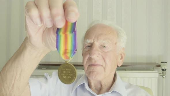 Senior man looking at an old medal