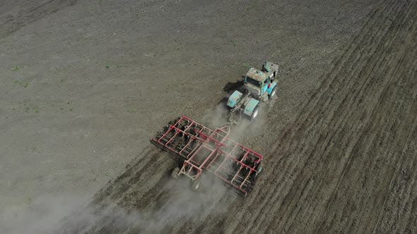 Thumbnail for A Tractor Cultivates the Soil in the Field.