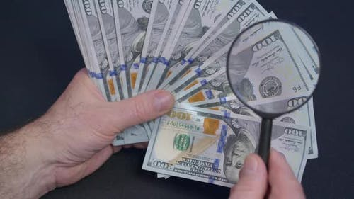 Person Checking Dollar Banknote for Authenticity with Magnifying Glass Close Up