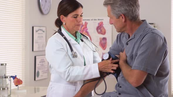 Thumbnail for Woman doctor checking elderly man's blood pressure