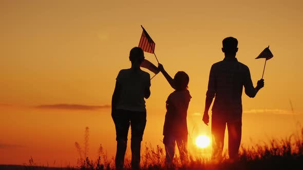 Thumbnail for A Family with American Flags in Their Hands Meets the Dawn