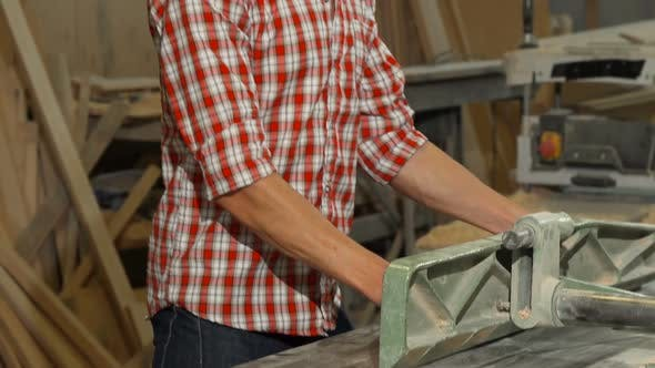 Thumbnail for Happy Male Carpenter Posing with a Piece of Wood at His Workshop