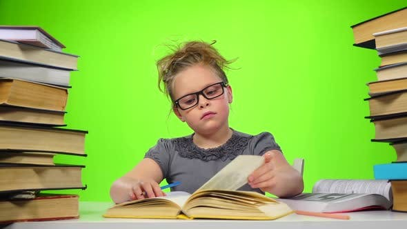 Cover Image for Girl Sitting and Leafing Through the Book. Green Screen. Slow Motion