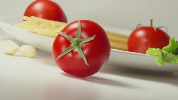 Thumbnail for Red Tomato Rolls On A Table Near Spaghetti And Garlic