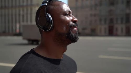 Happy Afro American Is Walking Along Wide Road in Big City and Listening To Music By Headphones