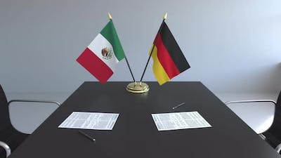 Flags of Mexico and Germany and Papers on the Table
