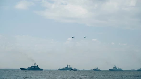 Helicopter Silhouettes Fly Over Naval Vessels at Parade