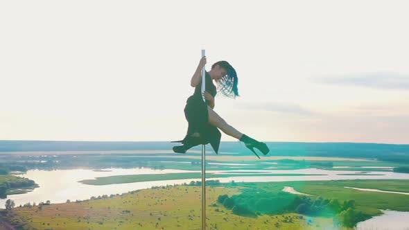 Thumbnail for Pole Dance on Nature - Attractive Woman with Long Blue Braids in Black Clothes Posing on the Top of