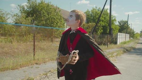 Junge in Halloween Kostüm auf der Suche nach Leckerbissen Outdoor