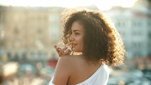 Thumbnail for A Young Attractive Woman with Curly Hair Flirting with Somebody on an Urban Background