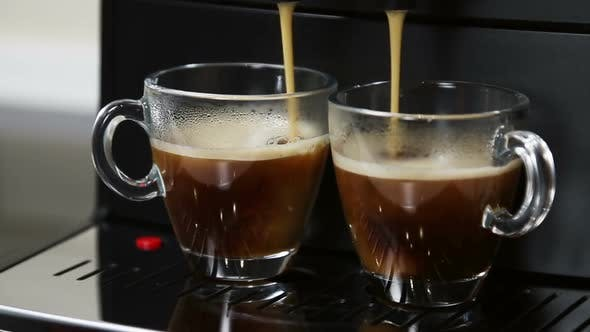 Coffee From the Coffee Machine Is Poured Into Glass Cups