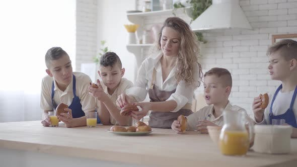 Thumbnail for Attractive Happy Woman and Her Four Teen Sons Eating Pies and Drinking Orange Juice in the Kitcken