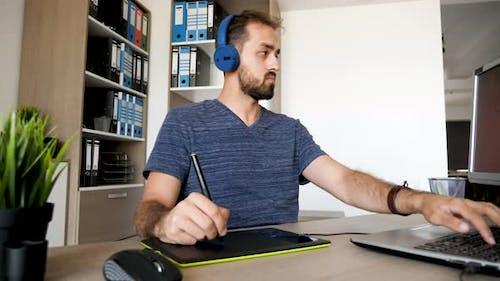 Man hört Musik in Kopfhörern und zeichnet mit einem digitalen Tablet