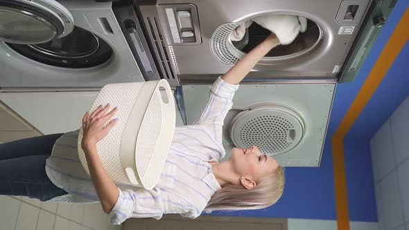 Woman with Blonde Hair Picks Up Laundry From the Washing Machine in the Laundry Room