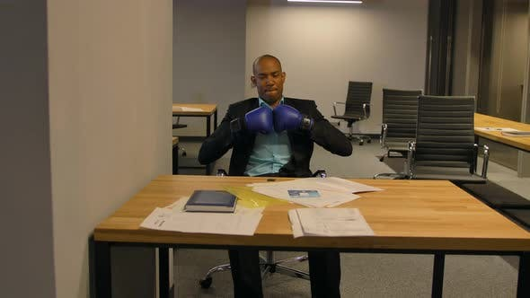 Afro-American Businessman Sit with Boxing Gloves in Office
