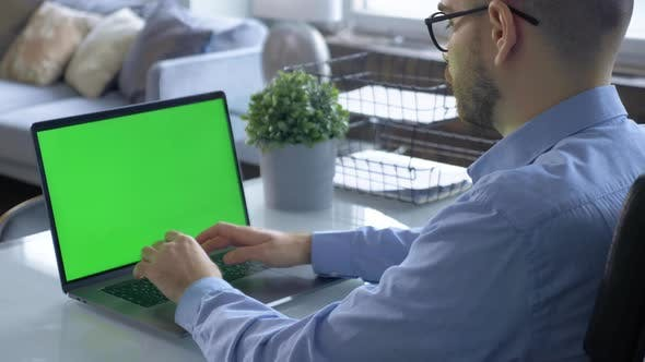 Rear View Of A Green Monitor Screen and A Young Man Working On An Online Learning Project