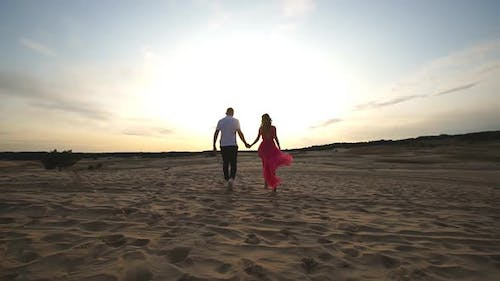 Camera Following to Young Pair Holding Hands and Walking Through Desert