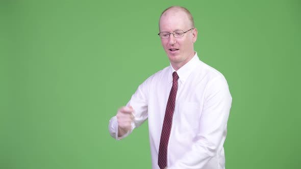 Cover Image for Happy Mature Bald Businessman Snapping Fingers and Showing Something