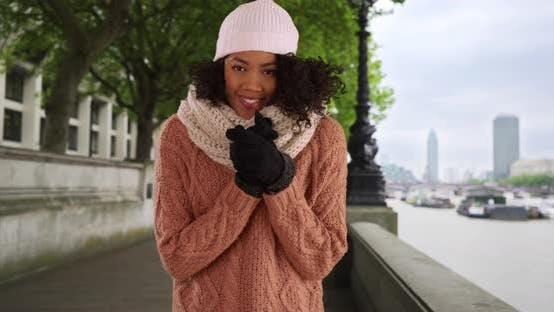 Thumbnail for Black woman on holiday in London laughs about chilly weather by the Thames