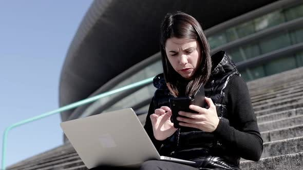 Thumbnail for Serious Woman Using Laptop and Smartphone
