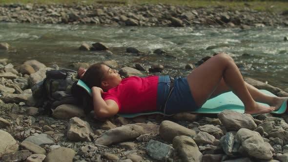 Peaceful Pretty African American Woman Backpacker Relaxing on Mountain Riverbank on Trek