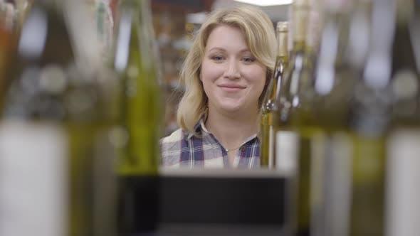 Thumbnail for Gesicht der positiven kaukasischen blond frau erscheint zwischen flaschen von weißwein, lächelnde lady nehmen