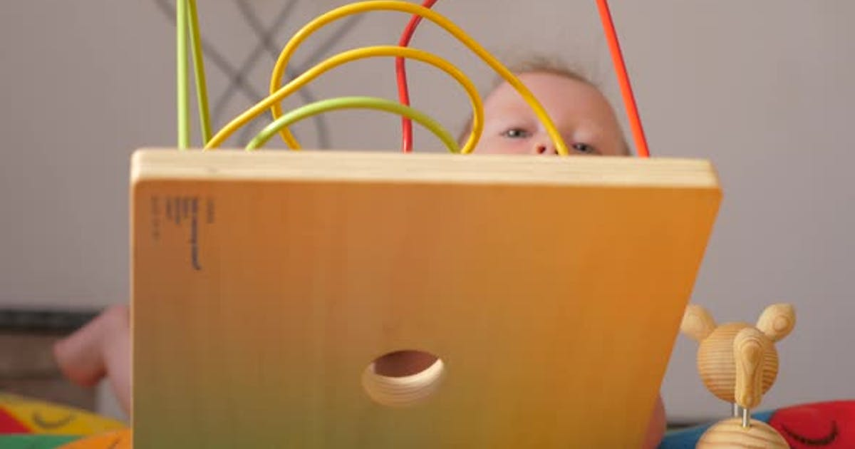 The baby develops fine motor skills. Montessori toy. Toddler playing with a Montessori toy.
