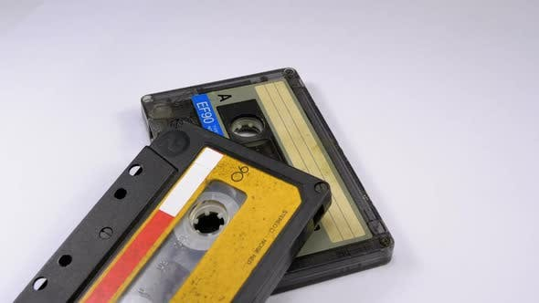 Cover Image for Two Audio Cassettes Rotate on White Background