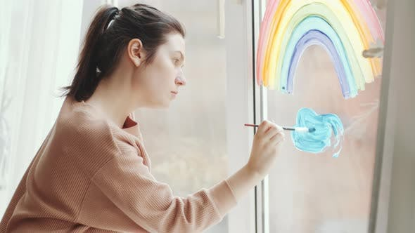 Young Talented Woman Painting on Glass Window at Home