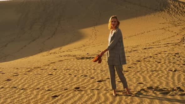 Attractive Woman in Business Attire Twirling in the Sand Dunes