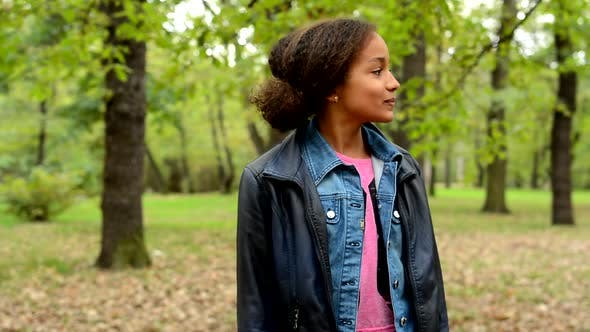 Thumbnail for Young African Satisfied Smile Girl Stand in the Park and Look Around Hersefl - Eye Contact