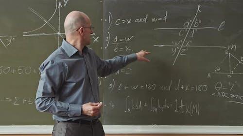 Maths Professor Solving Geometry Problems at Blackboard