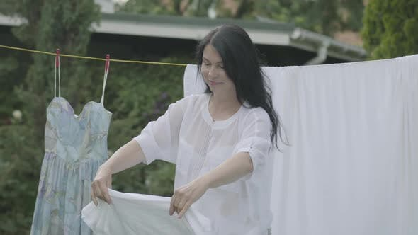 Thumbnail for Attractive Senior Woman with Long Hair Black Hair Hanging White Clothes on a Clothesline Outdoors