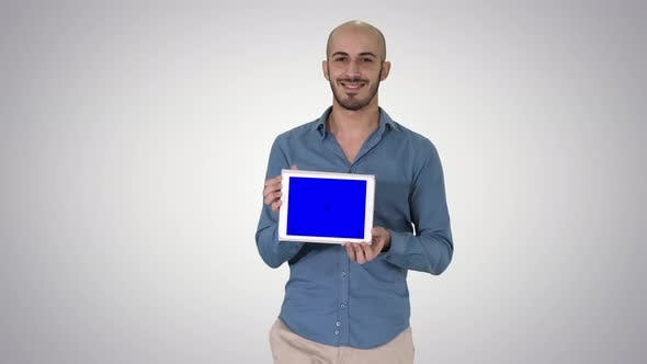 Thumbnail for Arab Man Walking and Showing Tablet Presenting Something on Gradient Background.
