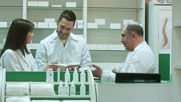 Thumbnail for Positive Team of Pharmacists Looking at Box of Tablet at the Hospital Pharmacy