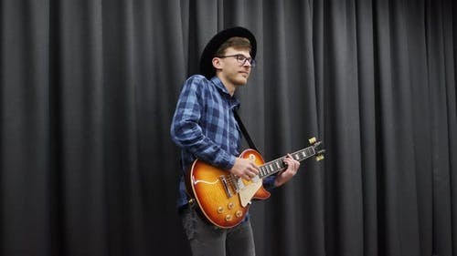 Musician performing song on guitar