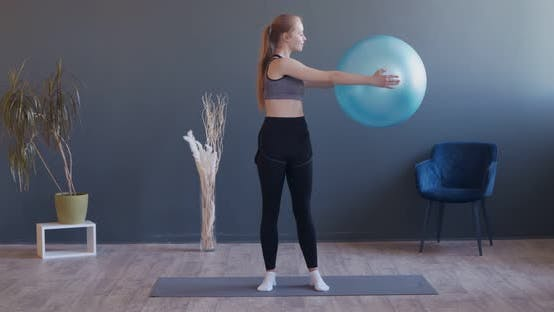 Young Sporty Woman Is Exercising By Doing Squats with Fitball at Hands in Training Gym