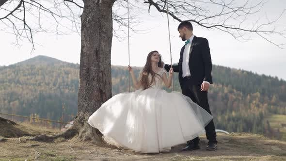 Thumbnail for Newlyweds. Caucasian Groom with Bride Ride a Rope Swing on a Mountain Slope