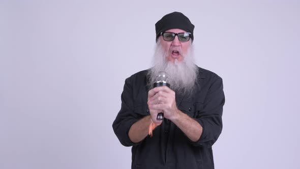 Thumbnail for Mature Bearded Hipster Man Singing with Microphone As Rock Star Concept