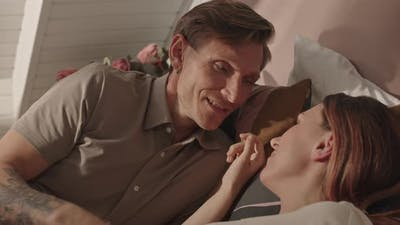 Man Talking to Wife in Bed