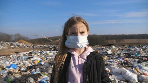 Thumbnail for Portrait of Little Serious Girl in Medical Protective Mask Stands Against the Background