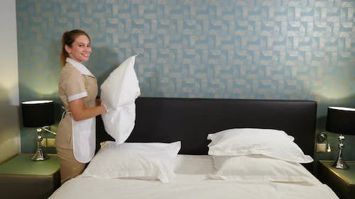Professional Cleaning Service. Smiling Chambermaid in Unifrom Making Bed and Beating and Arranging