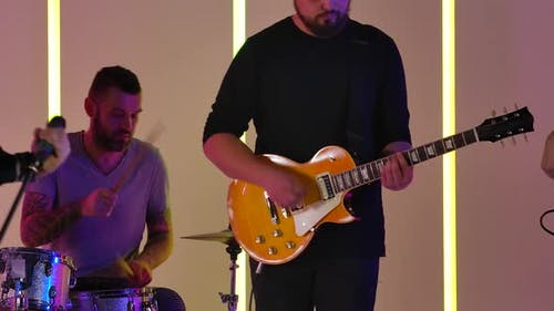 The Band Performs Their Music in the Studio Against the Backdrop of Multicolored Neon Lights