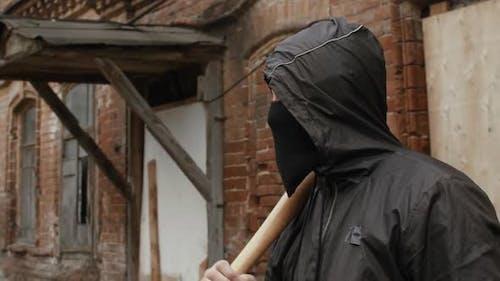 Street Hooligan in schwarzer Maske mit Baseballschläger auf krimineller Straße, die in die Kamera blickt