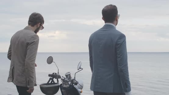 Two Elegant Caucasian Men Walking To River Bank in Slowmo with Scooter Steering Wheel at Front. Back