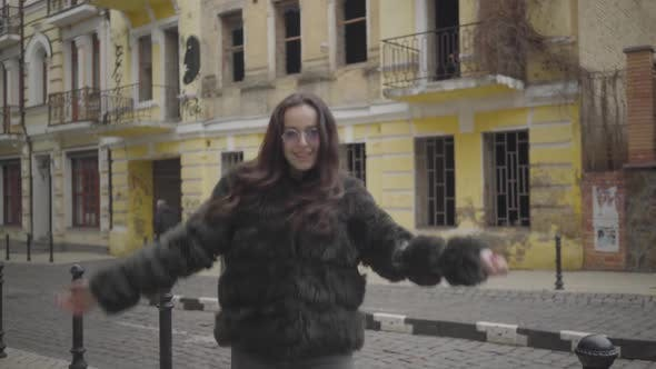 Thumbnail for Portrait of Joyful Stylish Girl in Fur Coat and Sunglasses Having Fun on City Street. Cheerful Young